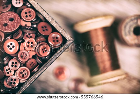 A close up of a box of red buttons, with a spool of red thread alongside. Filtered to have a faded matte finish with light leaks, and nostalgic style.