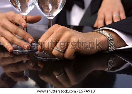 A close-up of a bride and groom's hands holding champagne glasses.