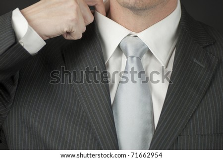 A close-up of a businessman adjusting his collar.