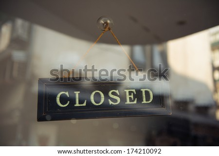 A close up of a 'CLOSED' sign hanging in a window - stock photo