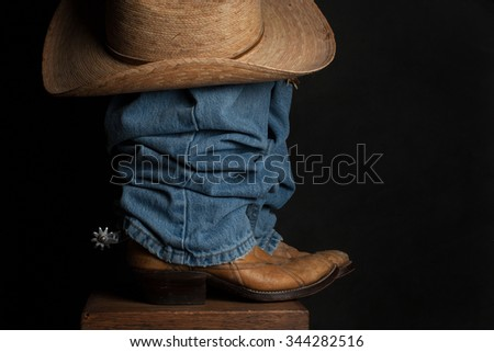 A close up of a cowboy boot, spur, and hat / Jeans and Cowboy Hat / A close up of a cowboy boot, spur, and hat against a dark background - stock photo