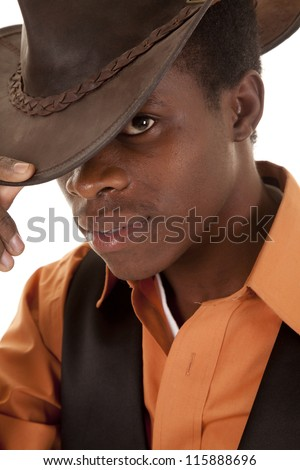 a close up of a cowboy holding on to the brim of his hat with a serious expression on his face - stock photo