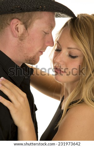 a close up of a cowboy with his woman her eyes are closed. - stock photo