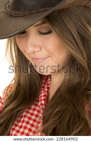 a close up of a cowgirl looking down. - stock photo