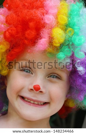 a close up of a cute, smiling toddler boy dressed up in a costume clown wig and face paint - stock photo