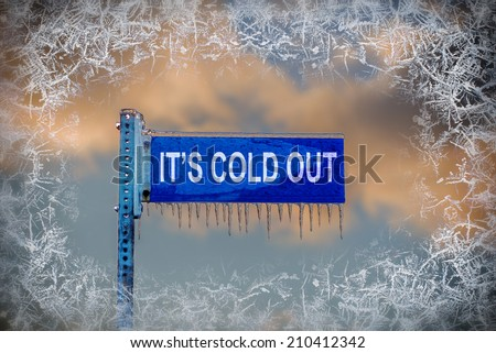 "A close up of a frozen blank blue street sign containing the text ""It's Cold Out!"" is covered in ice and icicles against a cloudy sky.  There is a border of frost surrounding the image.  - stock photo"