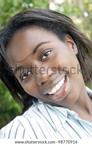 A close-up of a lovely young black woman outdoors.