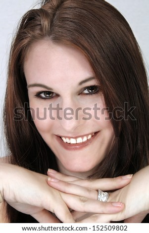 A close-up of a lovely young brunette with a bright, warm smile.
