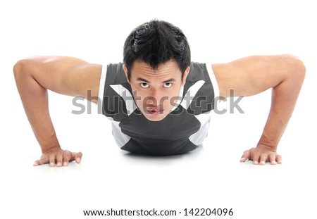 a close up of a man doing push ups with an intense expression on his face - stock photo