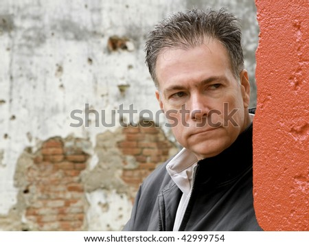A close up of a man peering mysteriously around the corner of a old building which has been painted red.
