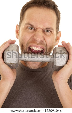 a close up of a man's face with a crazy expression on his face getting ready to bite a weight. - stock photo