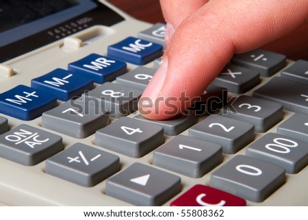 A close up of a man typing on a calculator