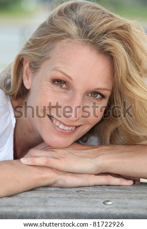 A close up of a middle-aged woman smiling at us. - stock photo