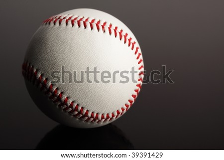 A close-up of a new baseball on a dark background, showing texture and detail.