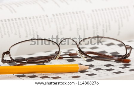 A close-up of a pencil and glasses on a crossword puzzle - stock photo