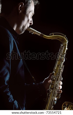 A close up of a saxophonist in a dark concert lit scenario - stock photo