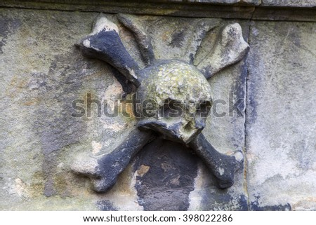A close-up of a skull and crossbones on a headstone in a graveyard. - stock photo