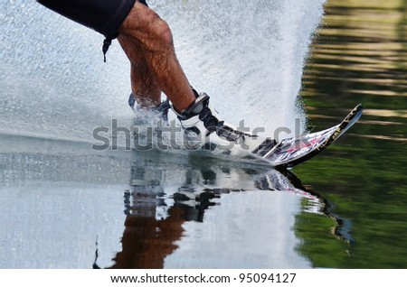 A close up of a slalom water skiers legs and skis with water splash. - stock photo