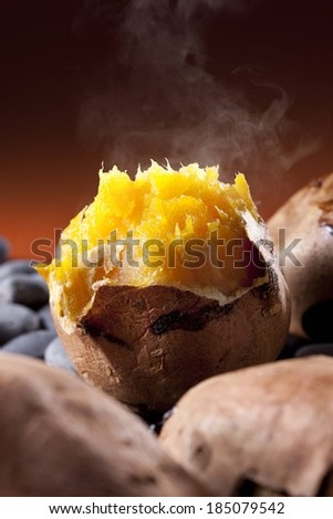 A close-up of a steaming baked potato amongst other potatoes. - stock photo