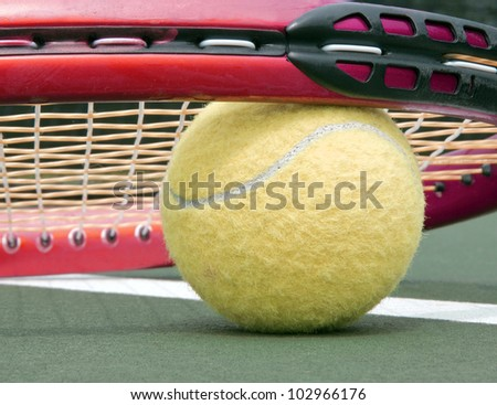 A close up of a tennis ball sitting on a tennis court under a racket