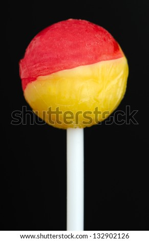 A close-up of a two-color strawberry and vanilla flavored lollipop against a black background - stock photo