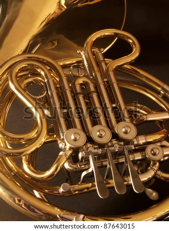 A close up of a very golden, concert french horn - stock photo