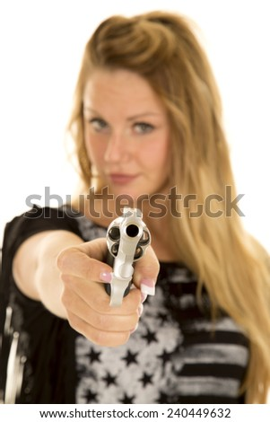 A close up of a woman holding onto a gun, pointing it at the camera. - stock photo