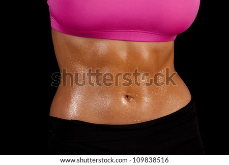 a close up of a woman's stomach with sweat dripping off of it - stock photo