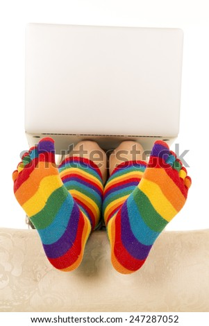 a close up of a woman with colorful socks on working on her laptop. - stock photo