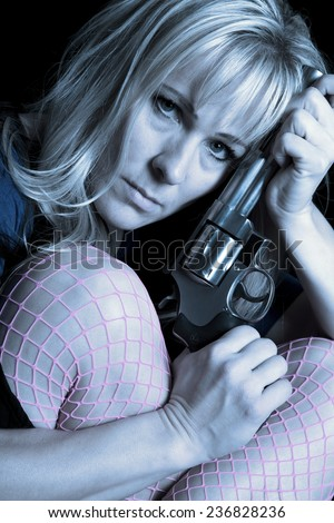 A close up of a womans head by knees in fishnet stockings holding a gun. - stock photo