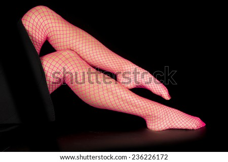 A close up of a womans legs in pink fishnet stockings. - stock photo