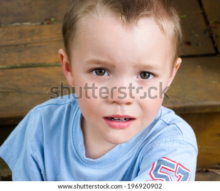 A close up of a young boy with a serious look of concern.  - stock photo