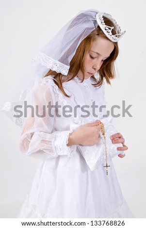 A close-up of a young girl in her First Communion Dress and Veil, pulling her rosary beads with a cross out of her purse