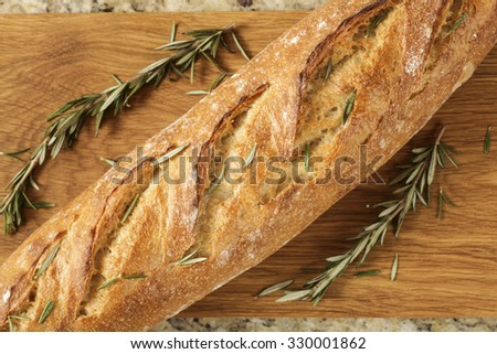 A close up of an artisan loaf of Italian bread next to natural herbs and mint on a cutting board. - stock photo