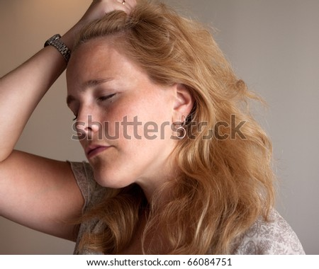 A close-up of an attractive adult woman with her eyes closed and pulling her hair back. - stock photo