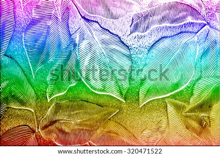 A close up of door or window glass embossed with a fancy leaf pattern and rainbow colors - stock photo