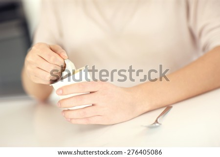 A close up of female hands opening yogurt in the kitchen - stock photo