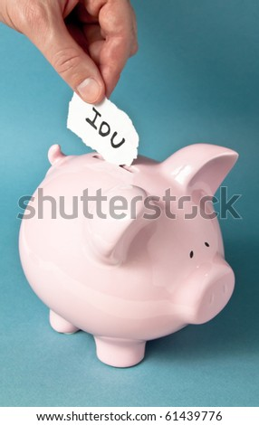 A close up of pink piggy bank on a blue background with a hand placing an IUO paper note into the bank - stock photo