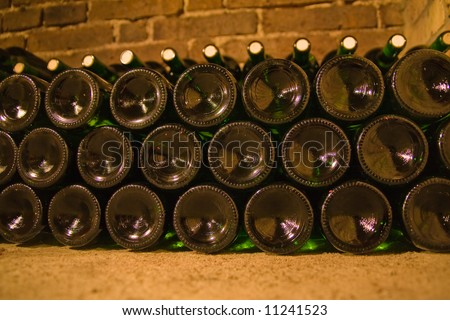 a close-up of stacked wine bottles in the cellar - stock photo