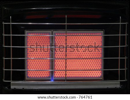 A close up of the heating ceramic of a switched on gas heater, with visible grill.