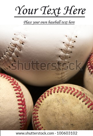 A close up of three baseballs and a softball nestled together with the top fading to white for copy space. - stock photo
