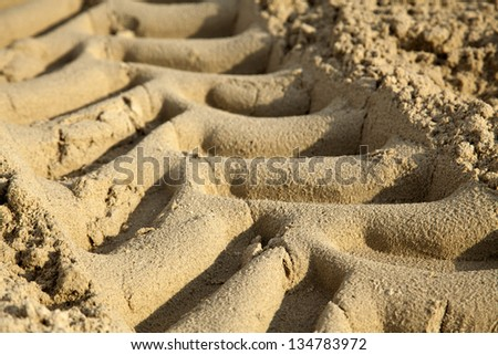 A close up of tractor tire tracks on beach sand. Shallow depth of field. - stock photo