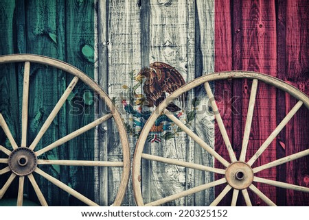 A close up of two antique wagon wheels lying up against a building with wooden siding depicting the flag of Mexico on its surface.  Filtered for a retro, vintage look.  - stock photo