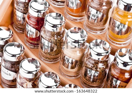 A close up on a spice rack full of a variety of different spices and herb  isolated on a white background. - stock photo