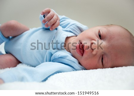 A close up photo of a beautiful and adorable new born baby boy, laying peacefully on a soft fluffy blanket. - stock photo