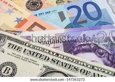 A close-up photograph of  United States and Euro and Sterling currency. - stock photo