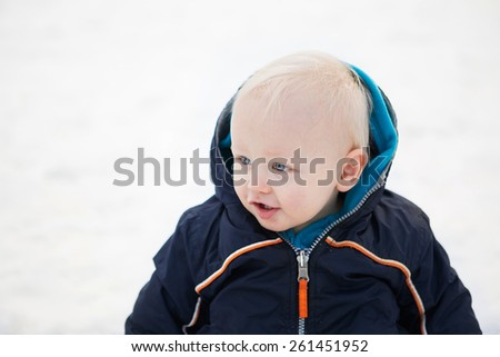 A close-up portrait of a baby boy happily sitting in the snow with his coat on - stock photo