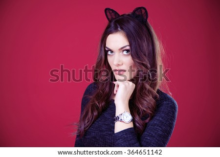 A close up portrait of a beautiful brunette girl with green eyes and black cat ears wearing a dark gray dress and glamorous watch with stones. Isolated. Bold red background. - stock photo