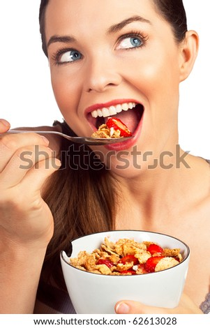 A close-up portrait of a beautiful young woman eating a healthy bowl of cereal with strawberries. Isolated over white.
