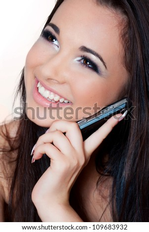 a close up portrait of a brunette beautiful girl talking on the phone - stock photo